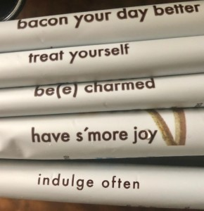 Candy labels reading: bacon your day better, treat yourself, be(e0 charmed, have s'more joy, and indulge often.